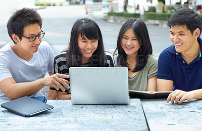 Buy stock photo Four young students sharing a laptop outside