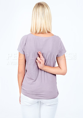 Buy stock photo Rear view of a young woman crossing her fingers behind her back