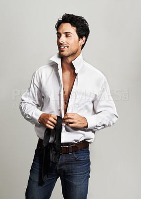 Buy stock photo A handsome young man buttoning up his shirt