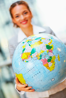Buy stock photo Young business woman holding the world globe, focus on globe