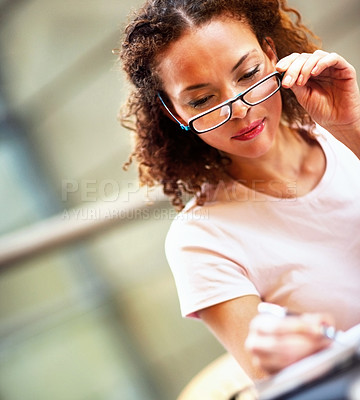 Buy stock photo Pretty African American business woman making a note, looking through her specs