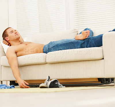 Buy stock photo Portrait of a tired young man resting on sofa in the living room
