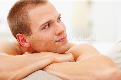 Buy stock photo Handsome young man relaxing on the couch, lost in thought