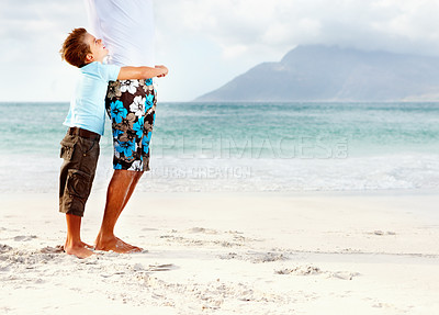 Buy stock photo Cute little boy at the beach with his arms around his father, seascape