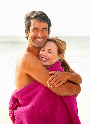 Buy stock photo Happy romantic couple embracing eachother while wrapped in a towel at the sea shore