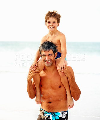Buy stock photo Portrait of a happy mature man carrying his son on his shoulders while at the beach