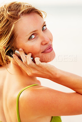 Buy stock photo Pretty young woman using a cellphone for communication while at the beach