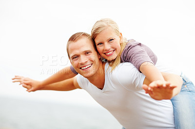 Buy stock photo Happy couple enjoying themselves out in the open, female on man's back