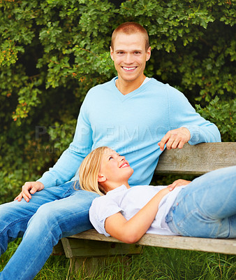 Buy stock photo Happy couple relaxing at the park, young woman lying on her boyfriends lap