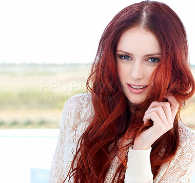 Buy stock photo A gorgeous young redhead standing outside smiling at the camera