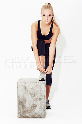 Buy stock photo A young blonde woman tying her shoelaces