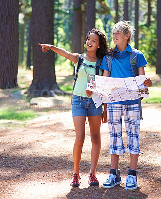 Buy stock photo An ethnic girl pointing towards something in the forest while her friend holds a map