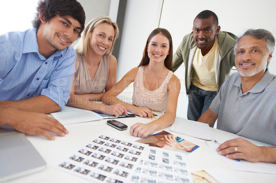 Buy stock photo A group of designers sitting around a boardroom table choosing images and smiling at the camera