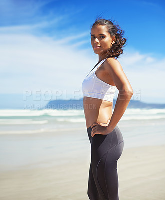 Buy stock photo A young jogger standing on the beach
