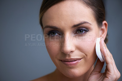 Buy stock photo An attractive young woman wiping the makeup from her face