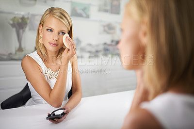 Buy stock photo A young woman applying make-up while sitting in front of the mirror
