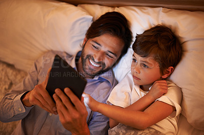 Buy stock photo A father reading a bedtime story to his son from an e-reader
