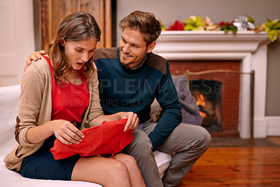 Buy stock photo A young woman receiving a christmas gift from her boyfriend