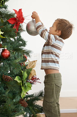 Buy stock photo Shot of a young boy decorating a christmas tree by himself