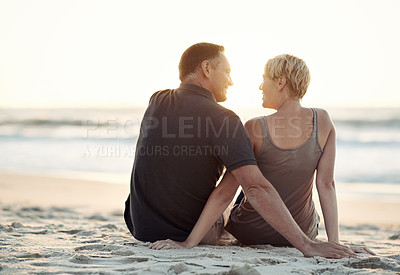 Buy stock photo A loving couple sitting on the beach - rear view