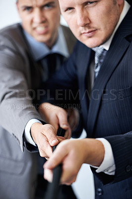 Buy stock photo Shot of two businessmen involved in a tug-of-war