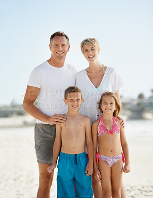Buy stock photo A happy young family standing on the beach while on vacation