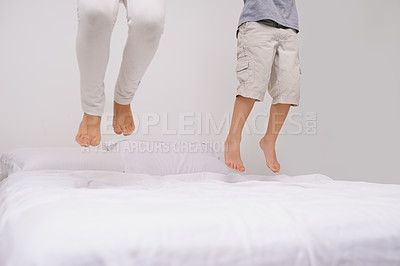 Buy stock photo Shot of the legs of a little boy and girl jumping on a bed