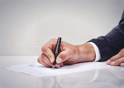 Buy stock photo Cropped shot of a businessman writing on a notepad