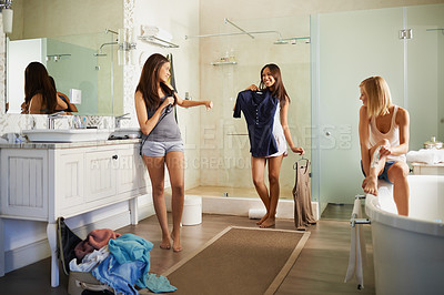 Buy stock photo A young woman asking her friends' advice on what to wear while they're getting ready