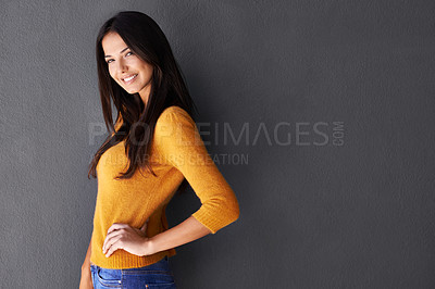 Buy stock photo Cropped portrait of an attractive young woman standing against a gray wall