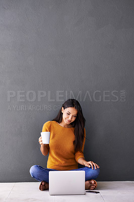 Buy stock photo A young woman drinking coffee while sitting on the floor with her laptop and mobile phone