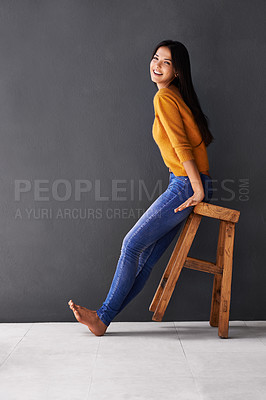 Buy stock photo Portrait of a happy young woman leaning sitting on a stool that's tilted back