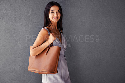 Buy stock photo Studio portrait of an attractive young woman holding her handbag