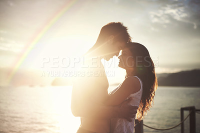 Buy stock photo Shot of an intimate young couple enjoying a vacation by the sea at sunset