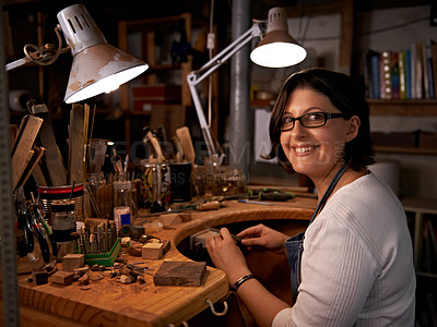 Buy stock photo Shot of a happy young woman sitting at a workbench