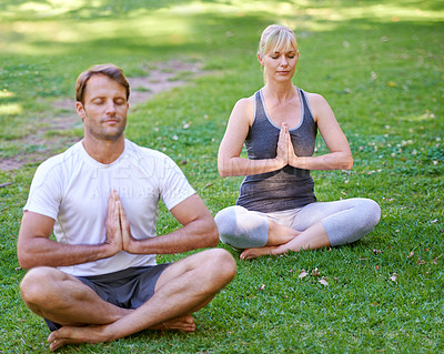 Buy stock photo Full length shot of an attractive couple doing yoga in the park