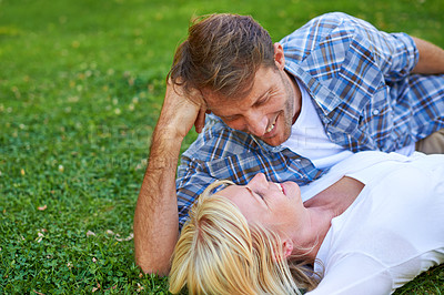 Buy stock photo Cropped shot of a couple lying on the grass