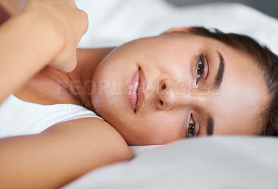 Buy stock photo Portrait of a young woman lying on her side in bed