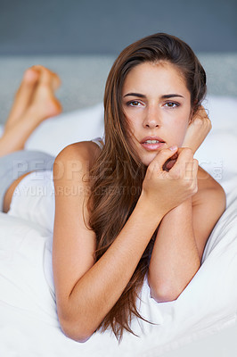 Buy stock photo Shot of a beautiful young woman lying on her bed