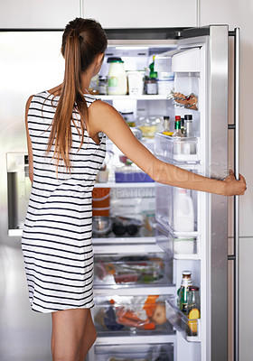 Buy stock photo A young woman looking for something in her refrigerator