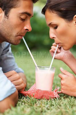 Buy stock photo Romantic couple enjoying a milkshake