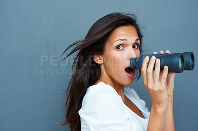 Buy stock photo Side view of woman looking surprised while holding binoculars against blue background