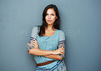 Buy stock photo Earnest woman with arms crossed against a blue background
