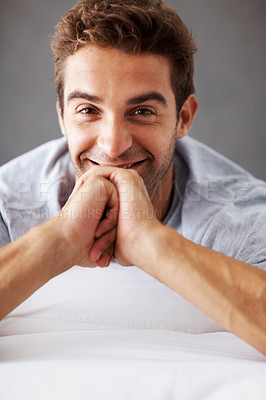 Buy stock photo Portrait of a happy young man lying on a bed at home