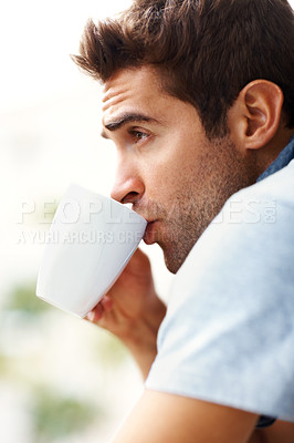 Buy stock photo Shot of a young man drinking coffee and looking away
