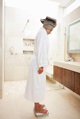 Buy stock photo Side view of a mature woman in a modern bathroom checking her weight