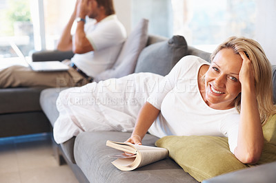 Buy stock photo Happy mature woman reading a book with man using laptop in the background at home