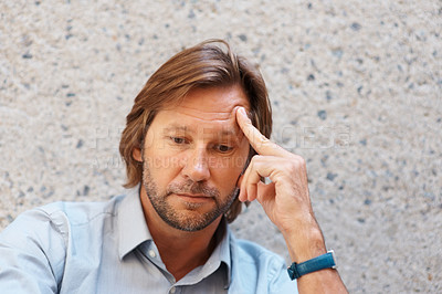Buy stock photo Closeup of a mature man in a deep thought looking down against wall
