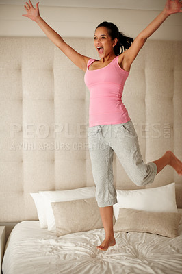 Buy stock photo Portrait of an excited young woman jumping on the bed with hand outstretched
