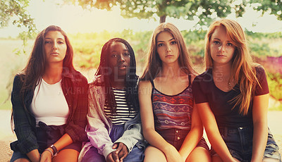 Buy stock photo A group of displeased looking teenage girls sitting outdoors
